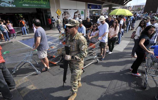 Colas. Residentes de Iquique deben esperar por horas para comprar alimentos. Un bidón de agua cuesta  200 dólares.