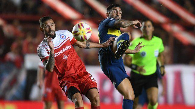 Con todo. El ex leproso Miguel Torren disputa fuerte el balón con Tevez