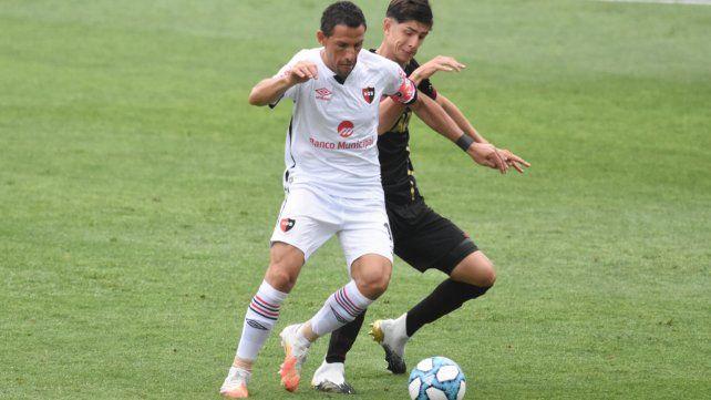 Maxi Rodríguez la cubre ante Belmonte en el partido que Newell's le ganó a Lanús por 4 a 2 en noviembre.