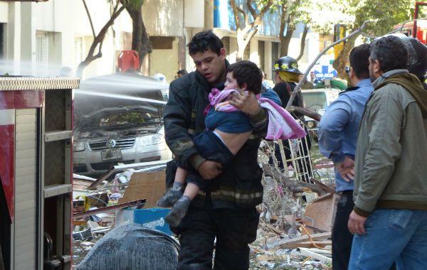 Un hombre saca en brazos a un niño tras la explosión en Salta al 2100. (Foto: A. Amaya)