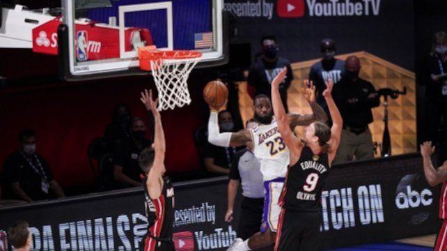LeBron James (23) pasa la bola bajo el tablero ante la marca de Kelly Olynyk (9) y Tyler Herro.