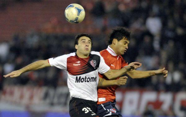 El delantero disputa una pelota contra un defensor de Independiente. (Foto: G. de los Ríos)