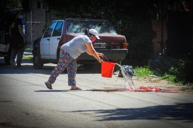 Una mujer baldea el manchón de sangre que dejó el ataque de un sicario contra Andrés Pizarro y Brian Soto
