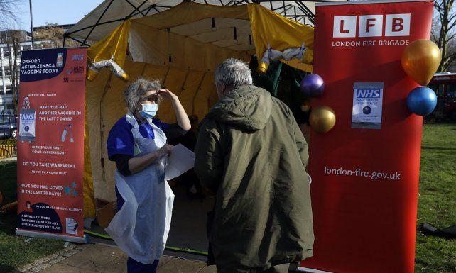 Una doctora habla con un paciente que llega para recibir su vacuna AstraZeneca Covid-19, durante un proyecto piloto de campaña de vacunación emergente llamado Vaxi Taxi en Kilburn, Londres.