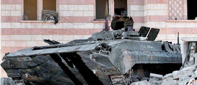 Un vehículo blindado de transporte de soldados del ejército sirio yace destruido en las calles de Aleppo. En Damasco se sucedían ayer las ejecuciones sumarias de presuntos guerrilleros.