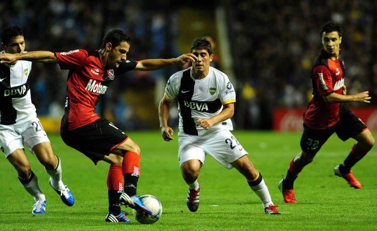 Maxi Rodríguez maniobra ante la marca de Erbes. (Foto: Héctor Río).