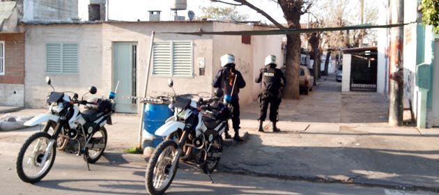 Policías montan guardia en una de las viviendas allanadas esta mañana. (Foto: Sebastián S. Meccia)