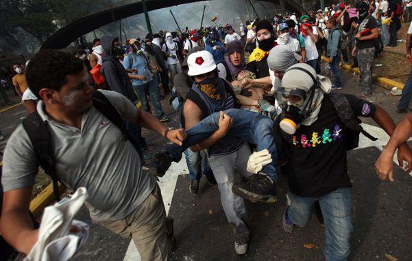 Caído. Un manifestante herido en una pierna es retirado por sus compañeros de las calles de Caracas.
