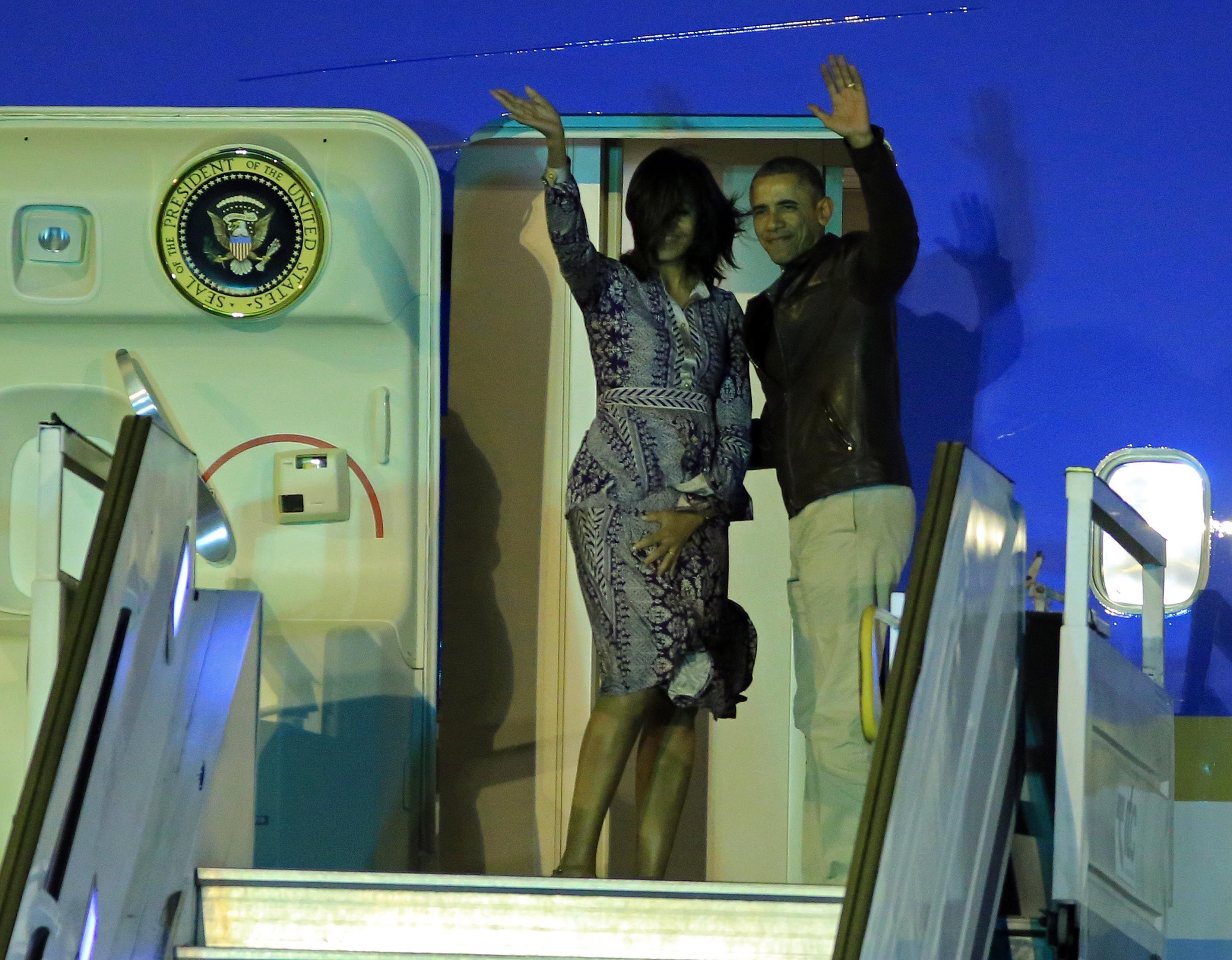Obama y su esposa saludan desde la puerta del Air Foce One
