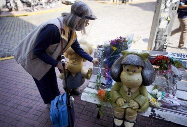 Una mujer deja flores en la escultura de Mafalda
