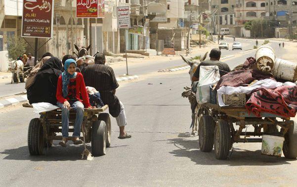 Exiliados. Civiles palestinos huyen de sus casas en el norte de Gaza ante la amenaza de más bombardeos.
