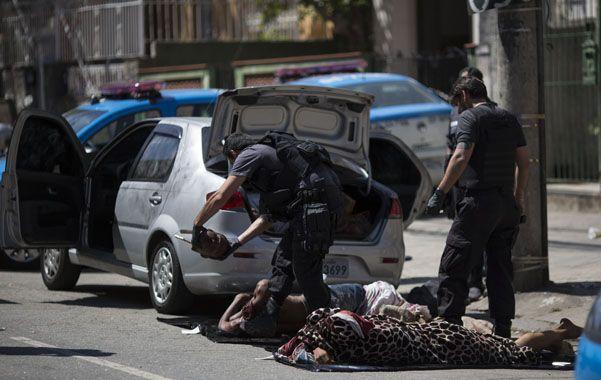Un policía retira la cabeza de unos de los cinco hombres asesinados.