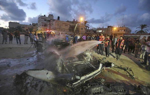 Bajo asedio. Bomberos apagan el fuego en los restos de un vehículo alcanzado por un misil israelí en Rafah.