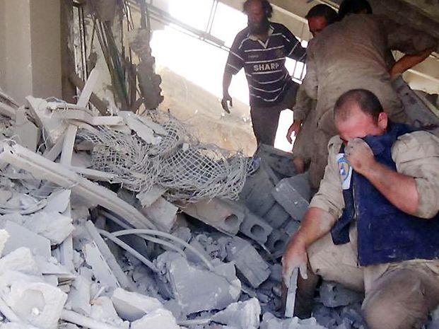 Destrucción. Rescatistas remueven escombros tras un bombardeo en Homs.