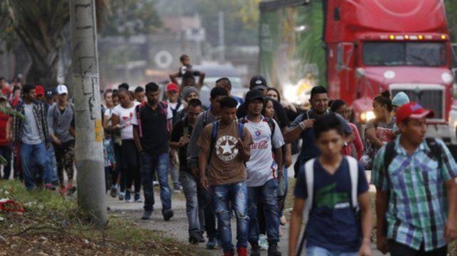 Los migrantes caminan por una carretera luego de haber salido de la ciudad hondureña de San Pedro Sula.