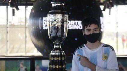 Un chico con la camiseta de la selección posa con la réplica de la Copa América en el Museo del Depirte.