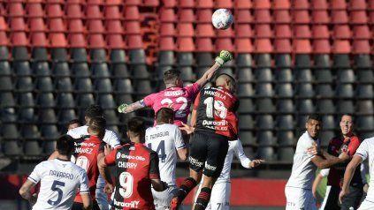 Herrera, el arquero de Talleres, rechaza con los puños ante la arremetida de Mansilla.