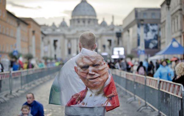 En el corazón. Un peregrino se envuelve en una bandera con la imagen del Papa polaco
