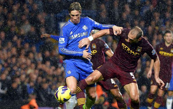 Fernando Torres y Pablo Zabaleta luchan por la pelota bajo la lluvia.