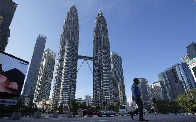 Un transeúnte camina por una calle vacía frente a las Torres Gemelas durante el primer día de la Orden de Control de Movimiento Total (MCO) en Kuala Lumpur