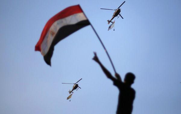 Simpatía. Un manifestante saluda el paso de helicópteros llevando banderas egipcias en apoyo a las protestas.