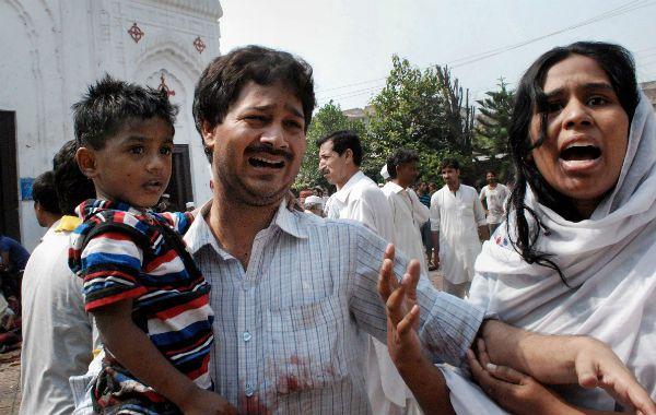 Un paquistaní cristiano llora sin consuelo por la muerte de un familiar tras un ataque suicida a la salida de la iglesia.