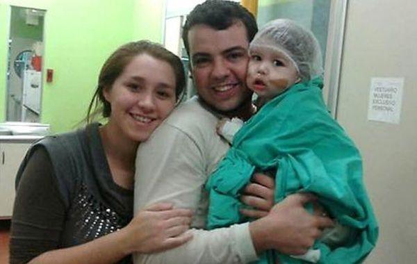 Renzo con sus padres. El niño correntino superó una cirugía de 14 horas.