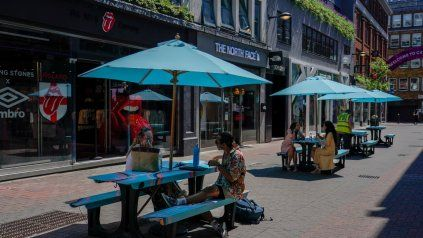 METRÓPOLIS. Poca gente sentada en mesas al aire libre en Carnaby Street, Londres. El desconfinamiento deberá esperar.