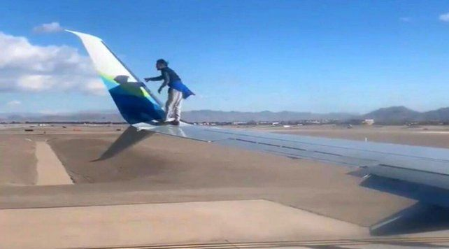 Hombre se sube al ala de un avión previo a despegar