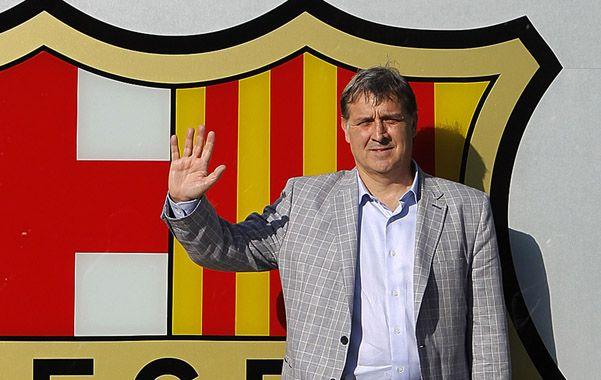 Allá vamos. Martino posó junto al escudo de Barcelona en las oficinas del club catalán. Muchos hinchas de Newells lo recibieron en el aeropuerto.