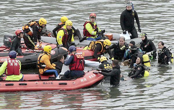 Penoso. Buzos rescatan a una de las víctimas fatales del vuelo de TransAsia.