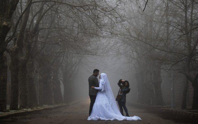 Una pareja de novios posan para una sesión de fotos de boda mientras una densa niebla envuelve la aldea de Sawfar, en la gobernación del Monte Líbano en el Líbano.