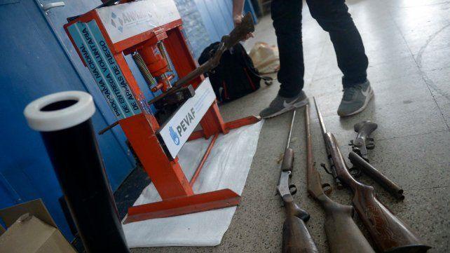 No va más. Un operario inutiliza en una prensa uno de los fusiles que los vecinos entregaron ayer en la sede del club Caova.