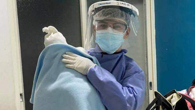 Emi Limido con el bebé al que ayudó a atender mientras asistía a una mujer que acababa de dar a luz. Tiene 18 años.