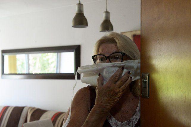 María Elena Biasín atiende con barbijo. Es contenidas por las vecinas y la portera del edificio céntrico donde vive.