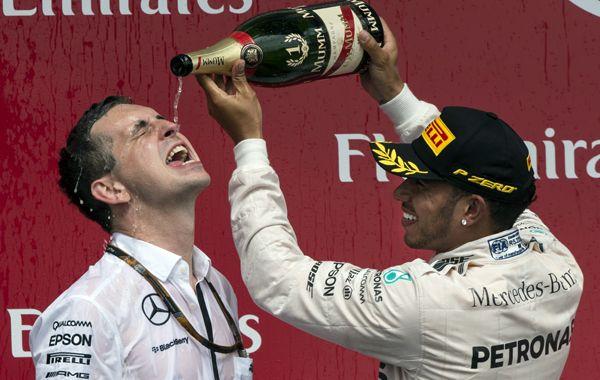 Hamilton celebra el triunfo con uno de sus mecánicos.