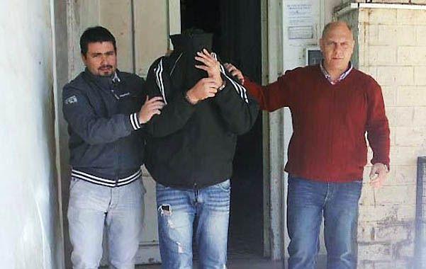 Miembros del cuerpo de la policía de la Unidad XVIII llevan a uno de los detenidos.
