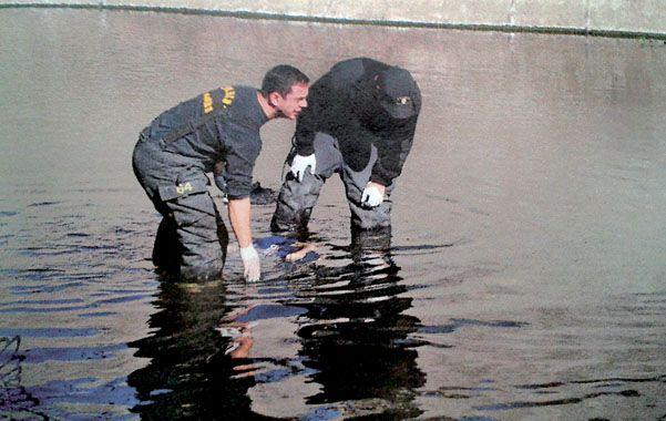 Empalme. Dos bomberos en el lugar del arroyo Ludueña donde cayó sin vida Marcelo Lares el 6 de junio de 2013.