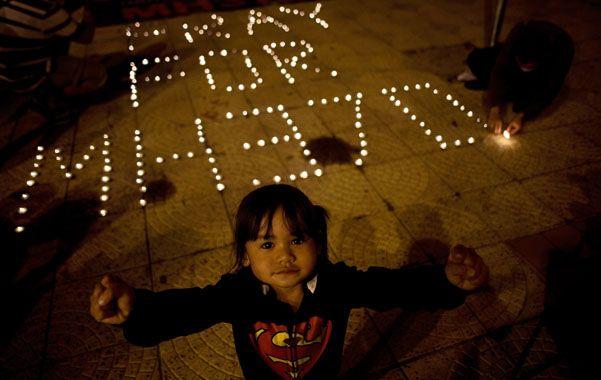 Velas en kuala lumpur. Un niña delante del homenaje al vuelo MH370.