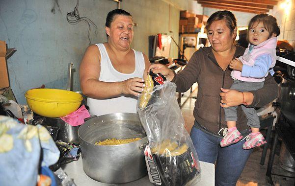 Menu del día. Fidela prepara junto a otra mamá los fideos que luego repartirá a las familias.