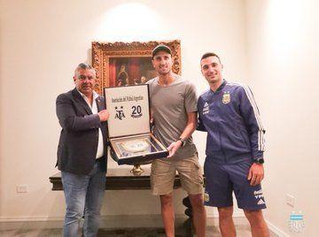 Chiqui Tapia y Scaloni le entregaron una plaqueta a Manu con el número 20.