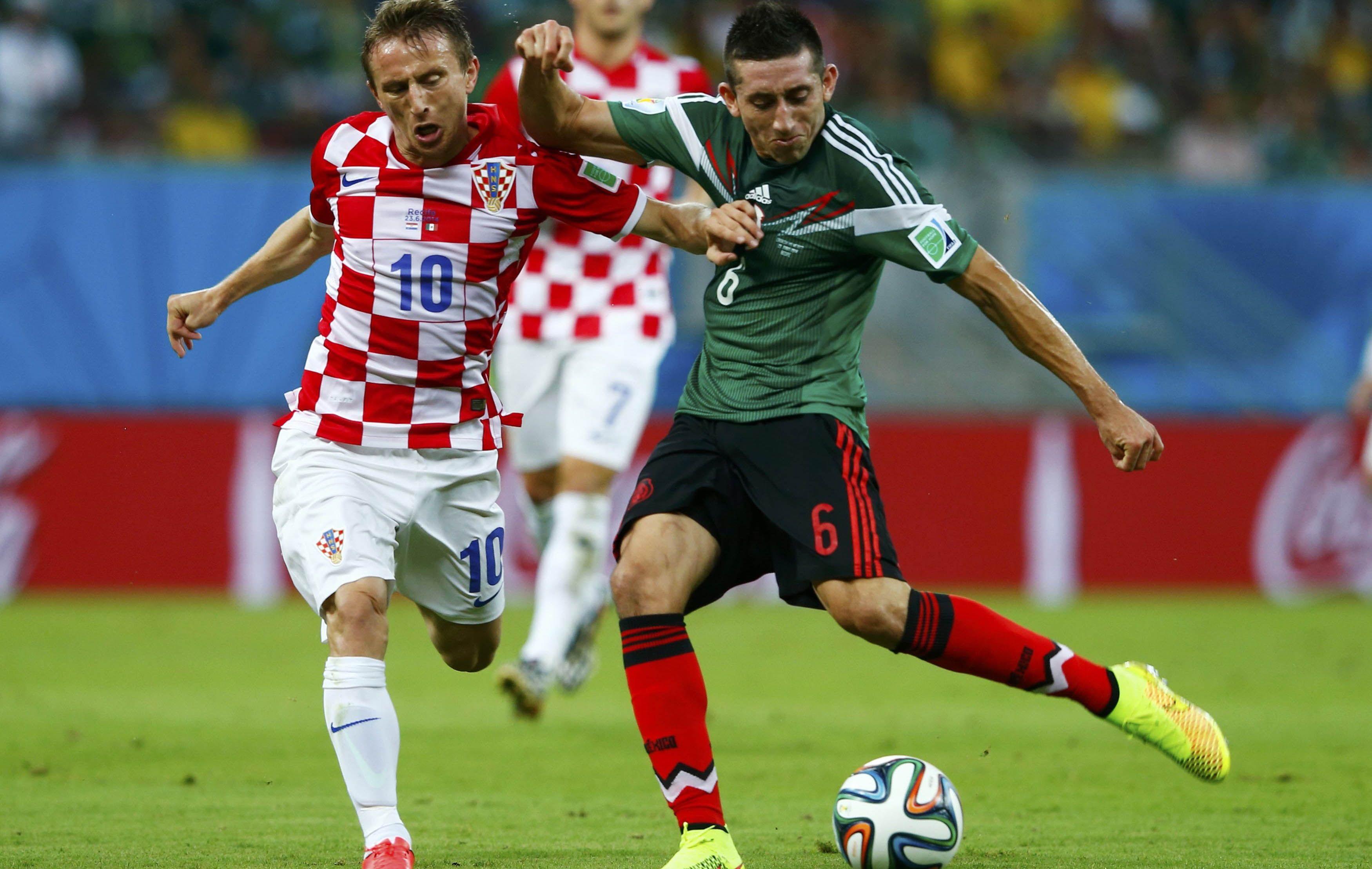 Herrera intenta rechazar ante la marca de Modric.