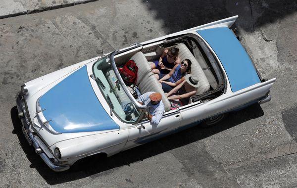 Turistas recorren en un viejo automóvil el centro de La Habana.