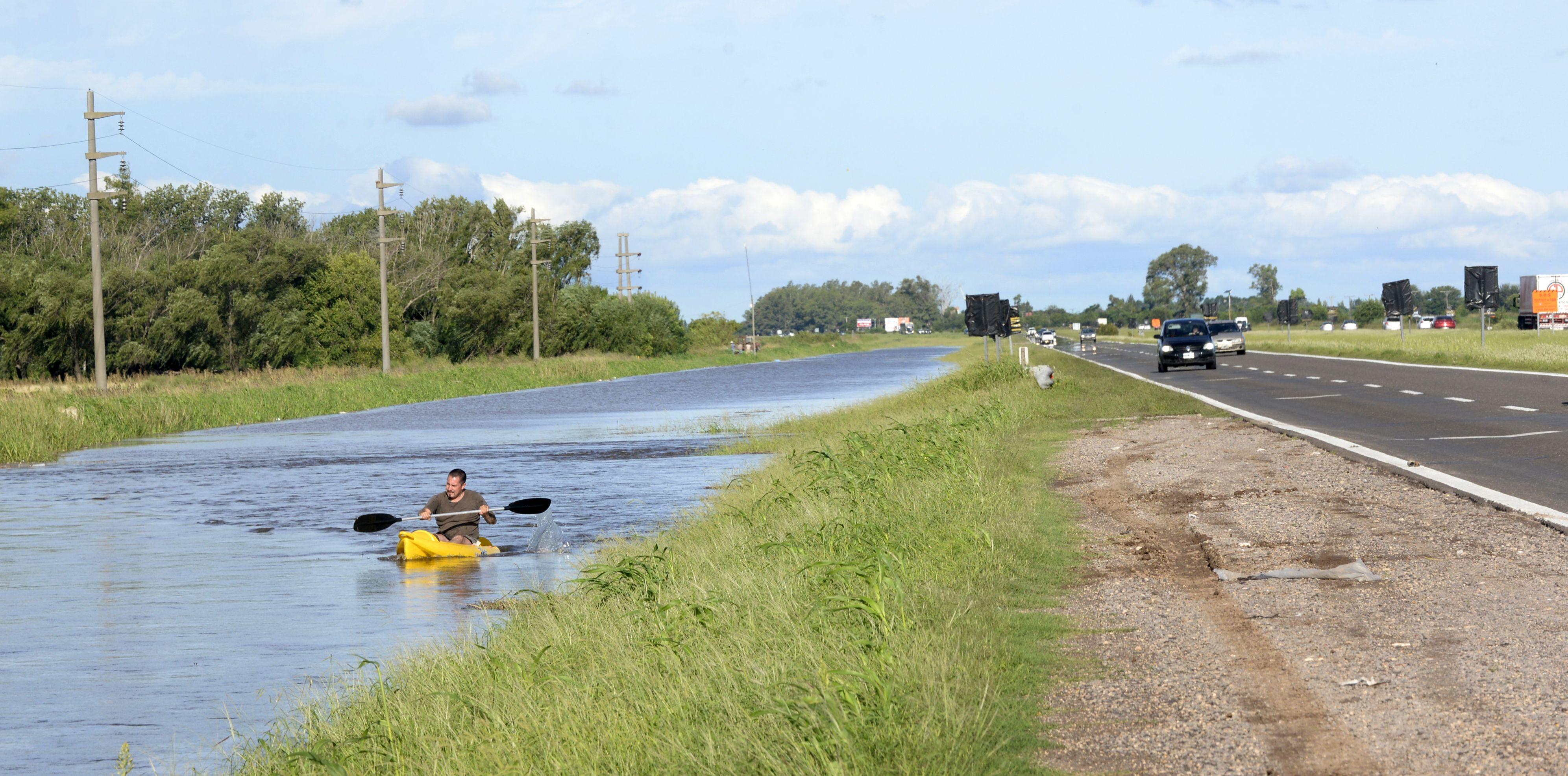 Ocurrente. Un kayakista aprovechó la laguna temporaria que se formó en la banquina de la autopista