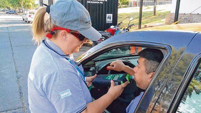 en acción. Una agente municipal le realiza un test de alcoholemia a un taxista en la zona de la Rambla Catalunya.