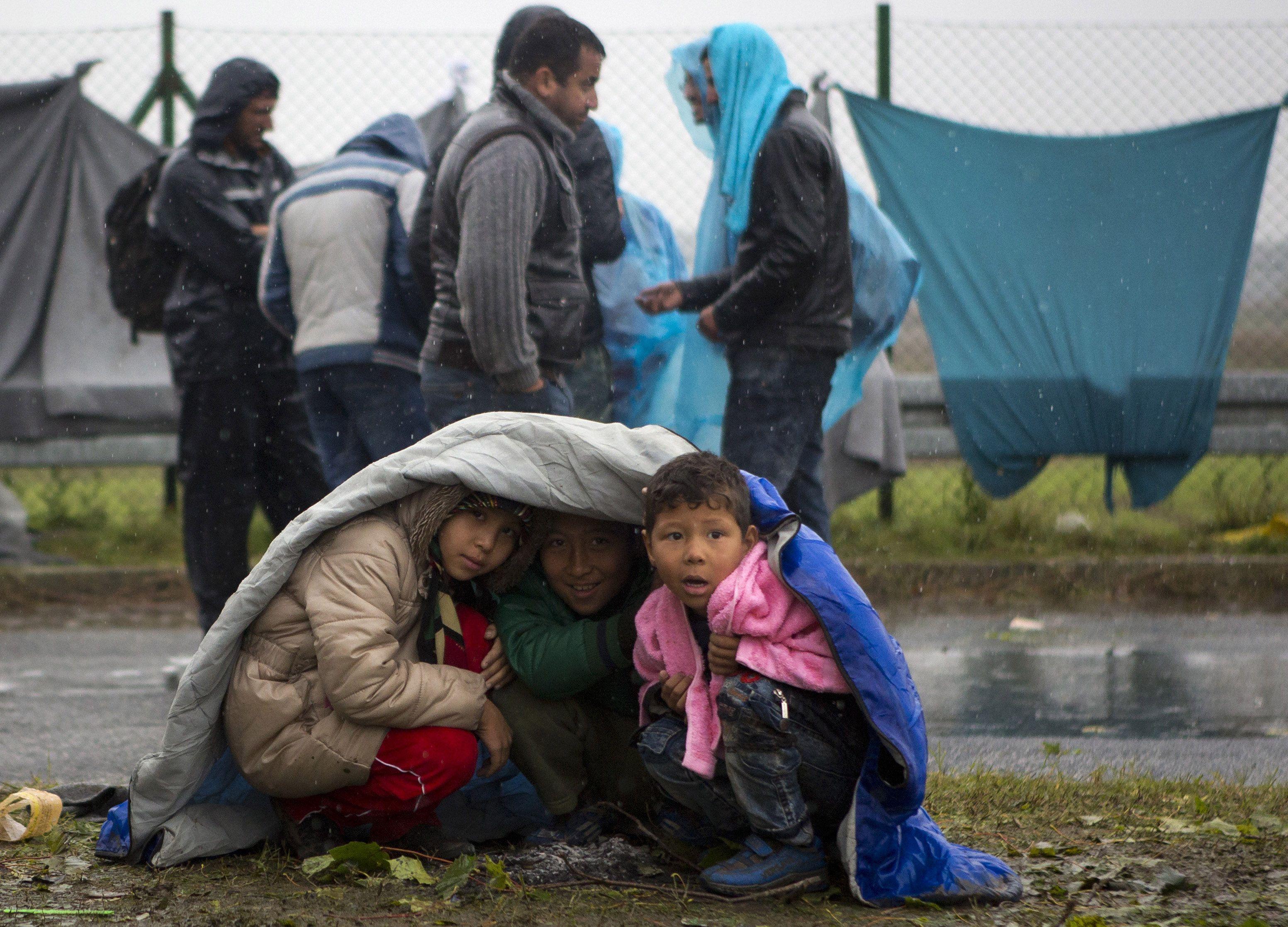 Unos chicos buscan refugio de la lluvia en el paso croata de Sredisce ob Dravi