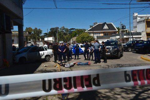 el final. Arijón y Mitre. El Chevrolet Corsa chocado y los dos jóvenes esposados y en el piso bajo custodia policial.