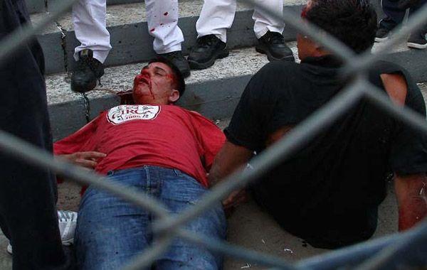 Un hincha de Quilmes brutalmente golpeado yace en el piso inconsciente.
