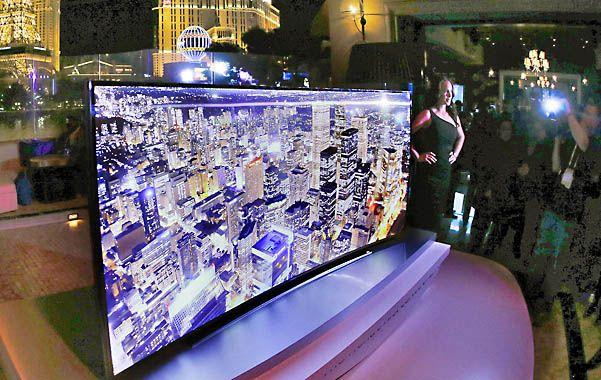 Una modelo posa al lado de la nueva pantalla curva de televisores de alta definición de 105 pulgadas (2