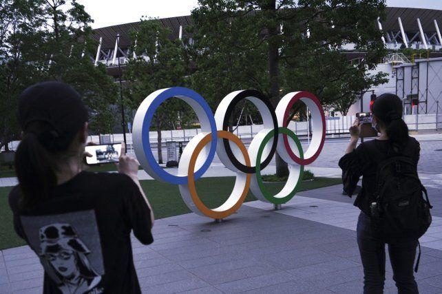 Mujeres toman fotos de los anillos olímpicos frente al Nuevo Estadio Nacional en Tokio.